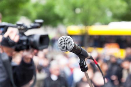 Photo pour Microphone in focus against blurred crowd. Filming street protest - image libre de droit