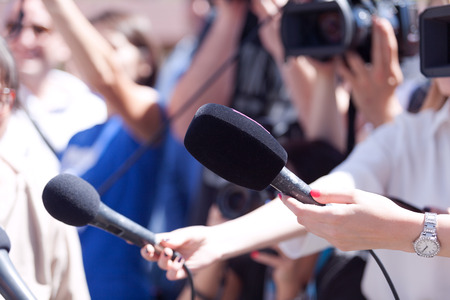Journalists holding microphones at a media event. Reporters at work.