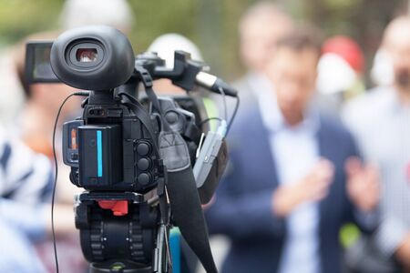 Photo for Video camera in the focus filming blurred unrecognizable person in the background - Royalty Free Image