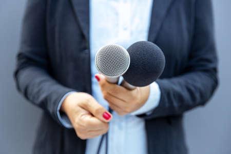 Photo pour Television reporter holding microphone during press interview. Journalism concept. - image libre de droit