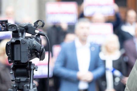 Photo for Focus on video camera filming news conference, blurred group of people holding protest banners in the background - Royalty Free Image