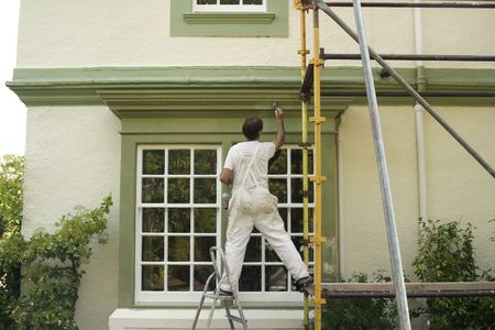 Painter decorating a house exterior.