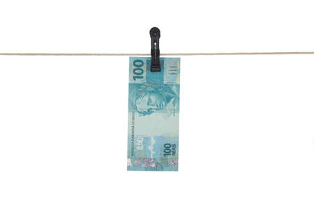 Photo pour Brazilian 100 Real bank note in a clothesline - Money laundering - dirty money  concept - isolated in white background - image libre de droit