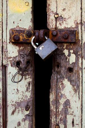 Old wood rural door with rusty padlock