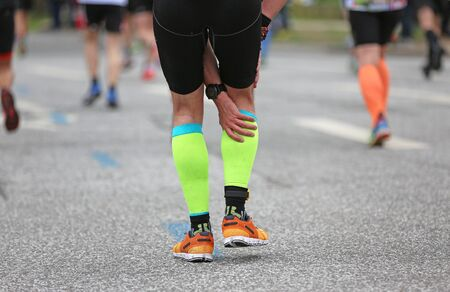 Foto de Marathon runner with a calf cramp - Imagen libre de derechos