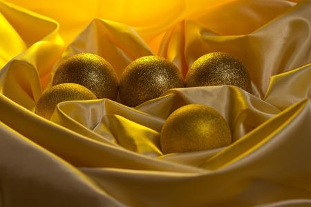 Christmas balls decoration on a yellow satin cloth