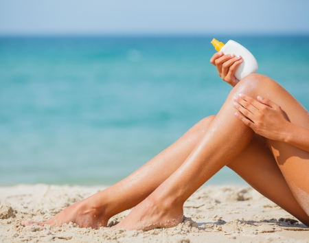 Photo pour Legs of young girl applying sunblock while sitting on a beach in summer  - image libre de droit