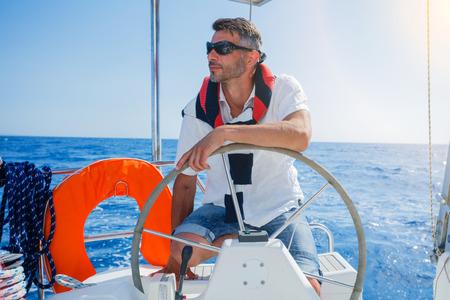 Photo pour Young man sailing yacht - image libre de droit