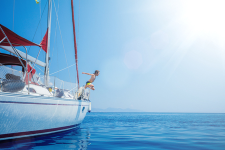 Boy jump in sea of sailing yacht on summer cruise. Travel adventure, yachting with child on vacation.