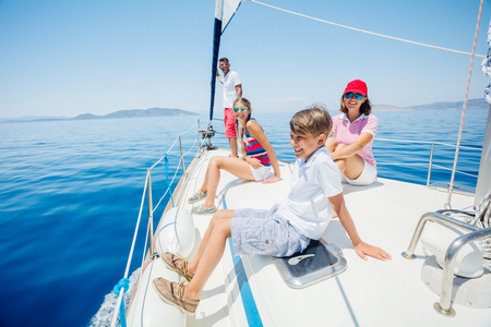 Photo pour Boy with his sister and mother on board of sailing yacht on summer cruise. - image libre de droit