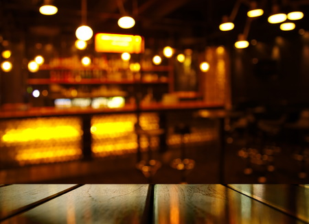 Foto de top of wood table with light reflection with yellow abstract blur bar or club in the dark night background - Imagen libre de derechos