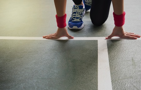 hands of woman runner with blue sport shoes at start white line on gymnasium floor background