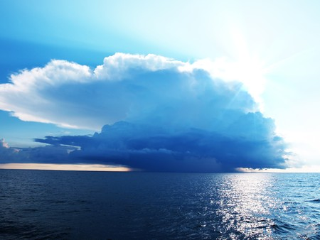 Bright blue sky with stormy clouds over a calm sea
