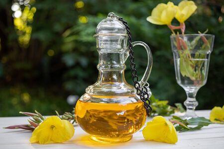 Photo pour Evening primrose oil in a beautiful bottle with fresh flowers - image libre de droit
