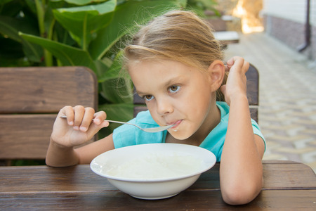 Six-year girl sitting at a table with a sour face and did not want to eat porridge for breakfast