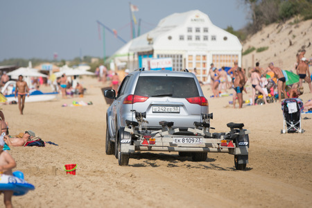 Anapa, Russia - September 20, 2015: passenger car with a trailer, riding on the beach with holidaymakers