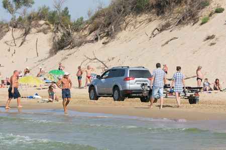 Anapa, Russia - September 20, 2015: Jeep with insolent driver rides on the beach with holidaymakers