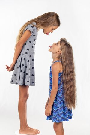 Foto de A girl stands on a chair, another girl stands nearby, show each other tongues - Imagen libre de derechos