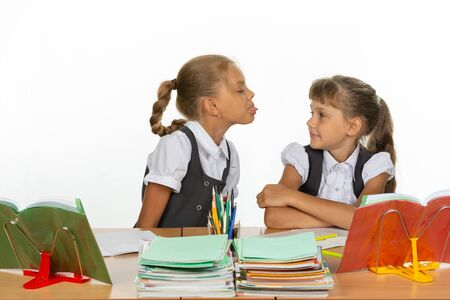 Photo pour Girl at her desk showed tongue to another girl - image libre de droit