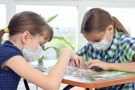 Foto de Two girls at home in isolation mode play board games - Imagen libre de derechos
