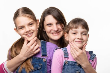 Photo for Mom cheerfully holds the children by the chin and looks in the frame - Royalty Free Image