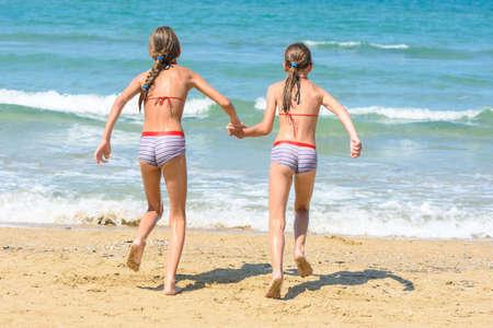 Photo pour Two little sisters running to swim in the sea, back visas - image libre de droit