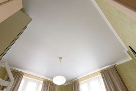Photo pour Stretch white matte ceiling close-up with a chandelier in the interior of a living bedroom - image libre de droit