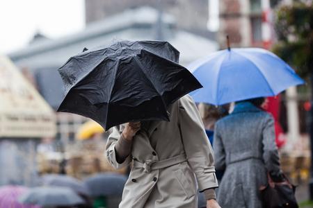 Photo pour people walking with umbrellas in the rainy city - image libre de droit