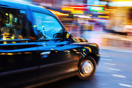 London Taxi in night traffic with abstract motion blur