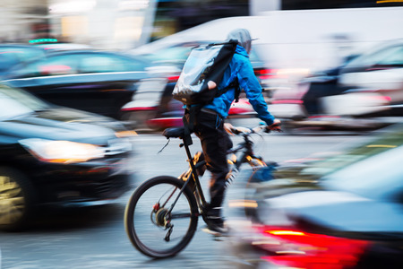 Photo pour picture of a bicycle messenger in busy city traffic with camera made motion blur effect - image libre de droit