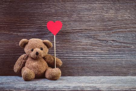 Foto de Teddy bear with heart sitting on old wood background. - Imagen libre de derechos