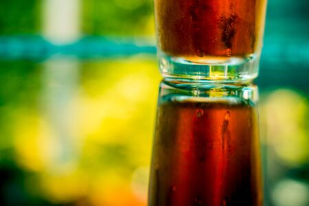 Photo pour Glass of cold natural ice tea at the bar – Fruity and refreshing beverage on a hot summer day reflecting on the mirror surface of the table – Colorful background of a sweet drink - image libre de droit