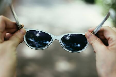 Photo pour Close-up shot o sf young person holding a pair of stylish black sunglasses outdoor – Woman hand with hipster eye ware on a grey background - image libre de droit