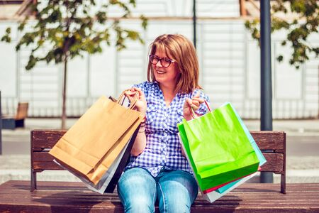 Photo pour Pretty woman sitting on a wooden bench in an italian city and laughing while she is holding colored paper shopping bags in both hands - image libre de droit