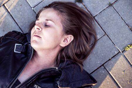 Photo pour Young woman lying down on ground with eyes closed – Sick or ill girl unconscious outside on concrete sidewalk – Victim of force abuse concept image - image libre de droit