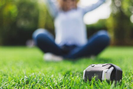 Photo for Portable speaker next to a girl relaxing in the lotus position - Office woman in shirt doing some yoga in nature with a wireless loudspeaker in front of her - Royalty Free Image