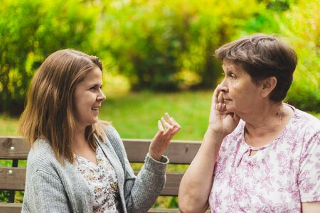 Photo pour Mother and daughter talking on a bench - Teen giving advice to an adorable old woman - Two women chatting outside - image libre de droit