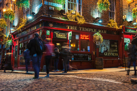 Photo for DUBLIN, IRELAND - NOVEMBER 11, 2014: Nightlife at popular historical part of the city - Temple Bar quarter. The area is the location of many bars, pubs and restaurants. People walking inside a pub - Royalty Free Image