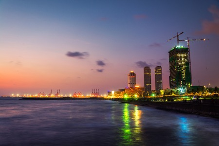 Photo for Cityscape of Colombo, Sri Lanka with modern buildings at night. Ocean waves at night and sunset cloudy sky. People at promenade area - Royalty Free Image