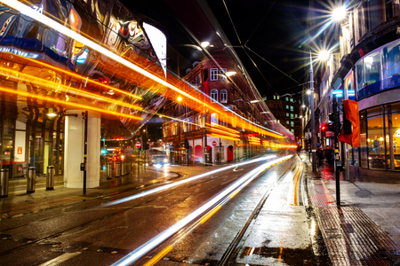 Photo for Birmingham, UK. Night life in the center of Birmingham, UK. Dark black sky with illuminated buildings, shops and stores. Tram trail lights - Royalty Free Image