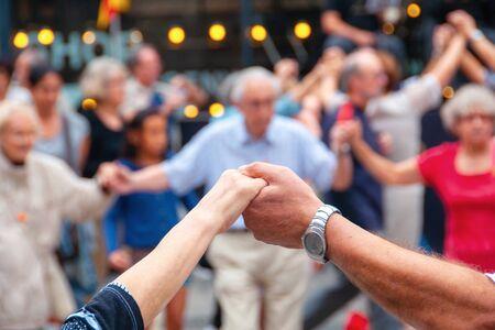 Foto de View of senior people holding hands and dancing national dance Sardana - Imagen libre de derechos