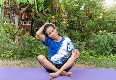Photo for Senior old woman warming stretching exercising on yoga mat outdoor on nature green background. Happy mature or elderly lady relaxing and enjoying warmup workout. Fitness and healthy lifestyle concept - Royalty Free Image