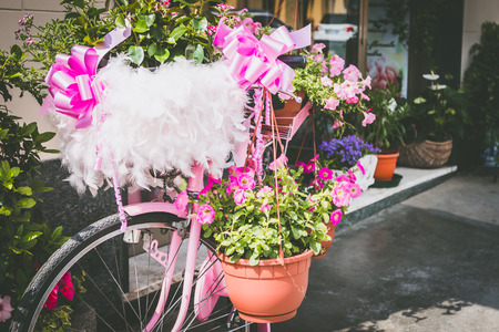 Particular of a vintage pink bicycle standing on the street - with many flowers.