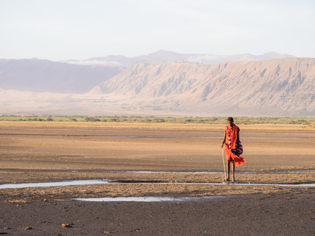Maasai warrior wearing traditional red clothes in the dried part of Lake Natron in the North of Tanzania, Africa.