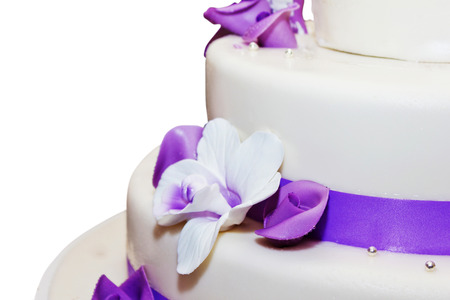 Tall wedding cake with purple ribbon and flower decorations
