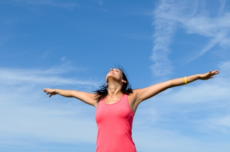 Happy girl with arms raised towards a blue sky on a sunny summer day.