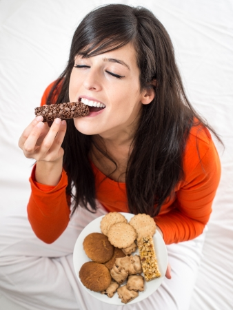 Beautiful hispanic woman tasting a delicious chocolate bar sitting on a white bed indoors. Pleasure of biting a crunchy snack.