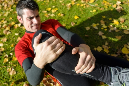Male athlete lying on the ground and suffering a tibia fracture. Grabbing his painful leg with two hands.