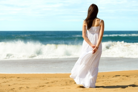 Young brunette woman in summer white dress standing on beach and looking to the sea  Caucasian girl relaxing and enjoying peace on vacation