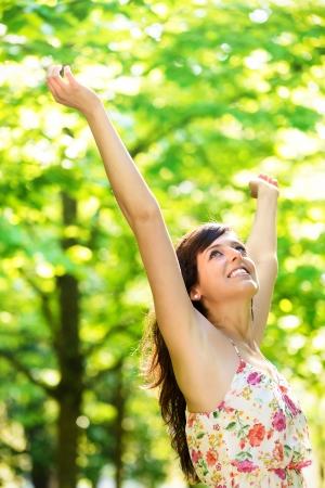 Happy young woman raising arms enjoying freshness of spring season in nature park surrounded by tress. Caucasian beautiful girl with open arms relaxing and celebrating life outdoors.